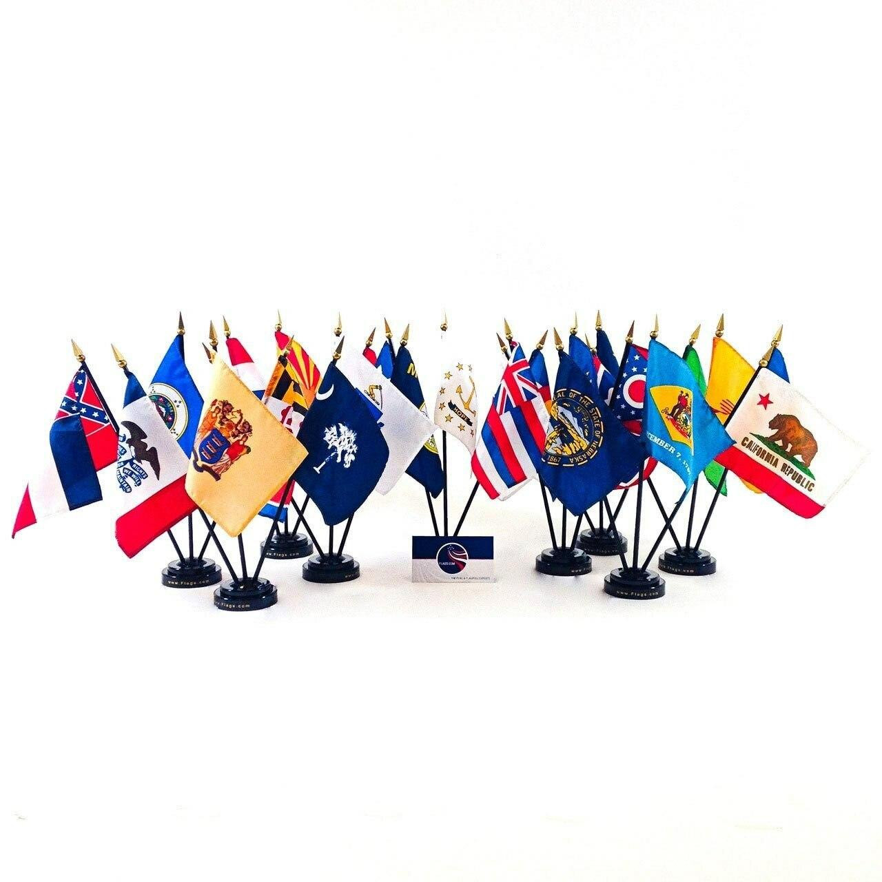 Different state stick flags are featured including in sets of 3 on Flags.com black plastic base. States featured include: California, Nebraska, New Mexico, Delaware, Iowa, South Carolina, Maryland, Hawaii, Ohio, Rhode Island, Montana, etc. Flags.com business card is centered in the middle of flag display. All flags have black plastic staffs and gold spears.