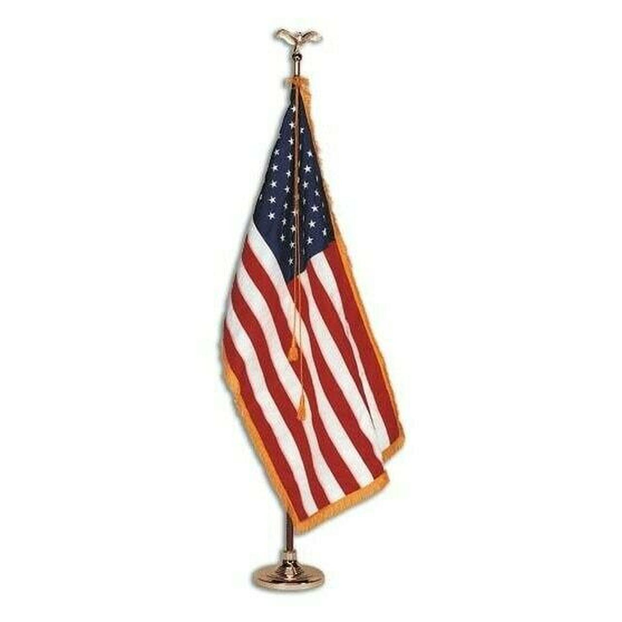 The American Indoor Display Flag set has a two-piece oak pole that sits in a gold stand with a gold eagle adorned on the top. The American flag with gold fringe hangs from the pole while a gold cord and tassel is draped atop the flag. The American Flag is a rectangular nylon flag with 13 sewn stripes alternating red and white and 50 embroidered white stars. The flag includes a sleeve opening to fit an indoor flagpole and gold fringe, decorative thread, around the border of the flag on three sides.
