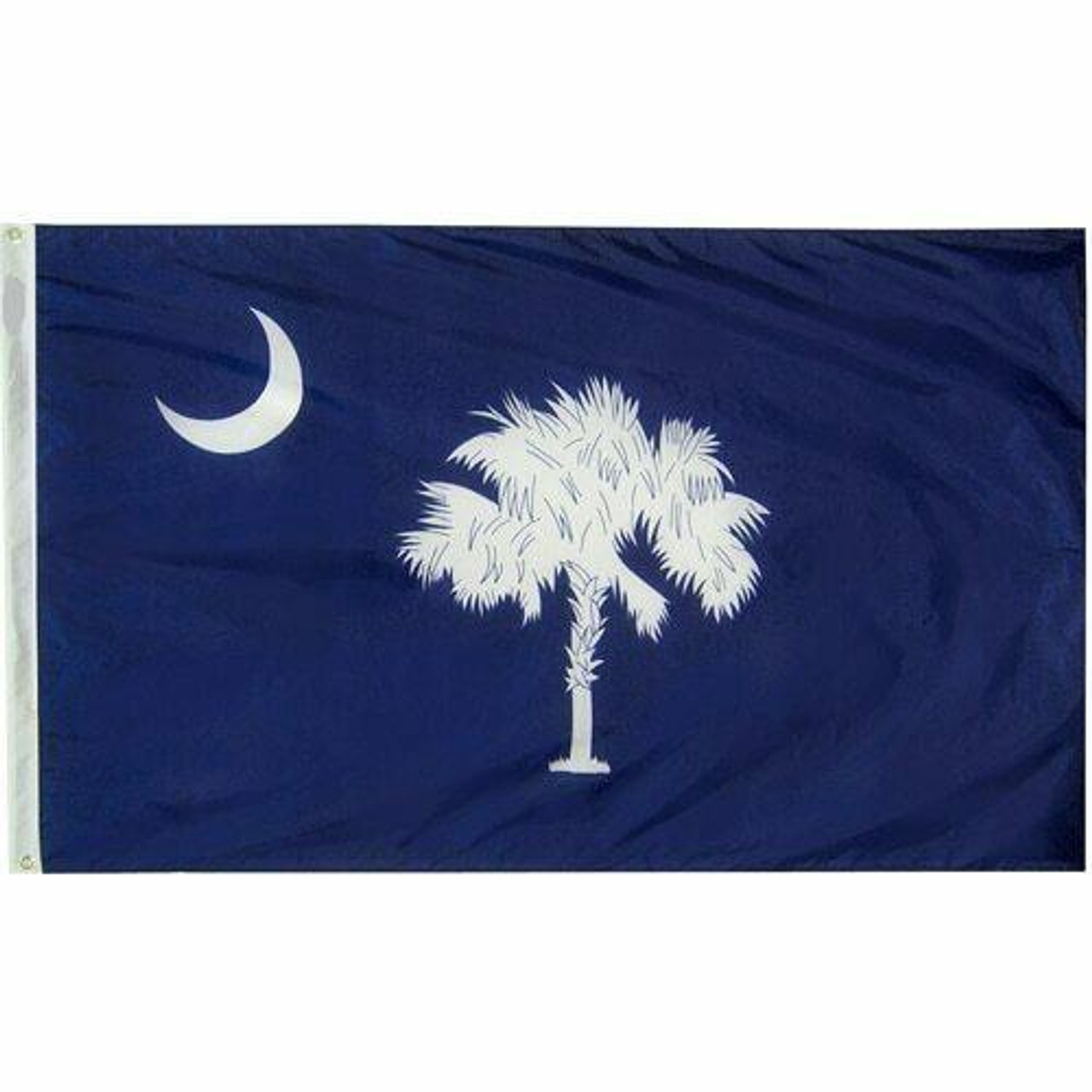 The South Carolina flag consists of a navy blue background with a white palmetto tree in its center and a small white crescent in its top left corner. On the left side of the flag is a durable canvas header with brass grommets for easy attachment to flagpoles.