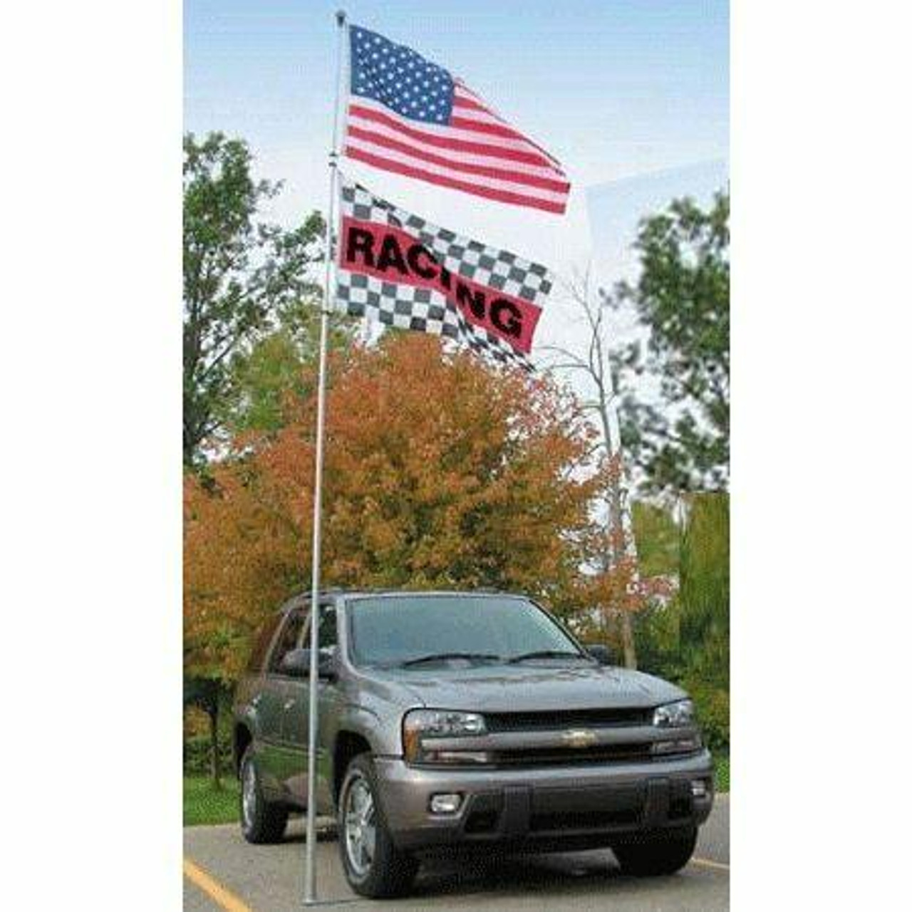 """The collapsible aluminum Flagpole To Go is attached to its flagpole ground mount or wheel stand. The stand is carefully positioned under the tire of an SUV, which firmly holds it into place. Attached to the flagpole is a red, white, and blue American flag. Hanging below that flag is a checkered black and white flag with a red stripe running horizontally across its center. In the stripe is black text reading """"RACING""""."""