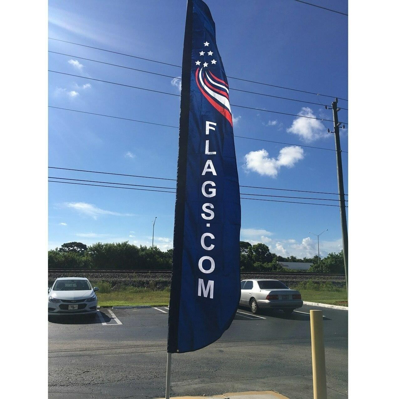 The telescoping fiberglass flagpole is outside again, fully extended featuring a Flags.com feather flag, great for catching customers' eyes.
