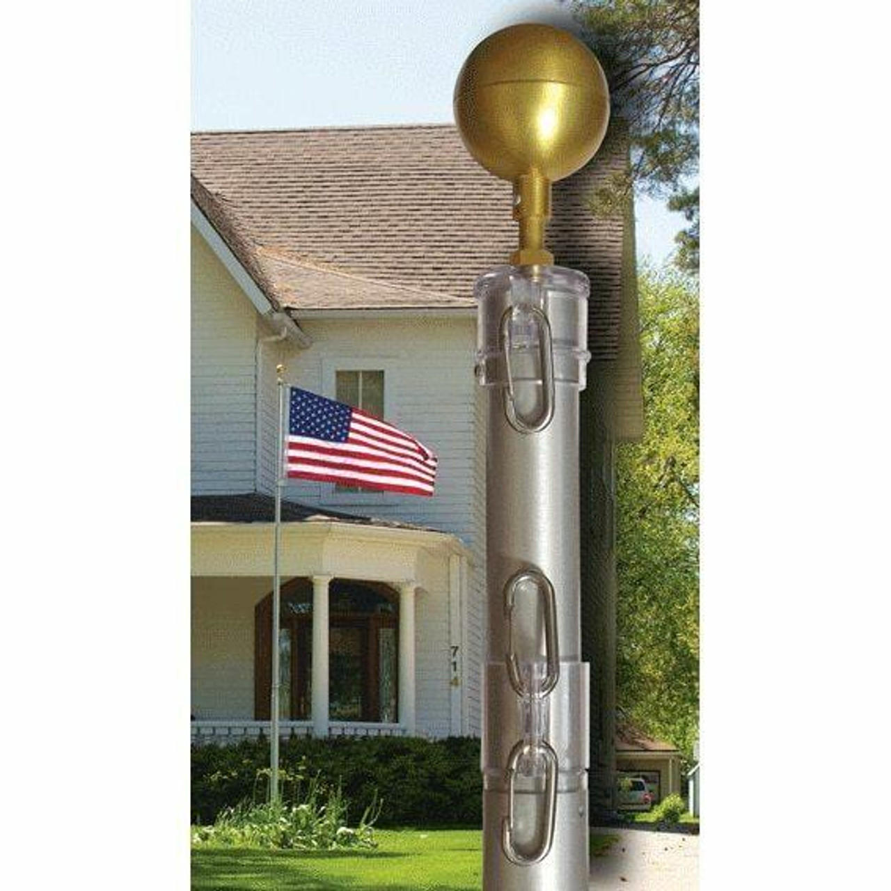 The 25 foot Telescoping Flagpole stands in front of a house with an American flag sitting atop it. In the photo's foreground is a close up shot of the top of the flagpole, showing the gold painted aluminum decorative ball, the flagpole's polycarbonate cap, and halyard snaps for easy attachment to your flagpole.