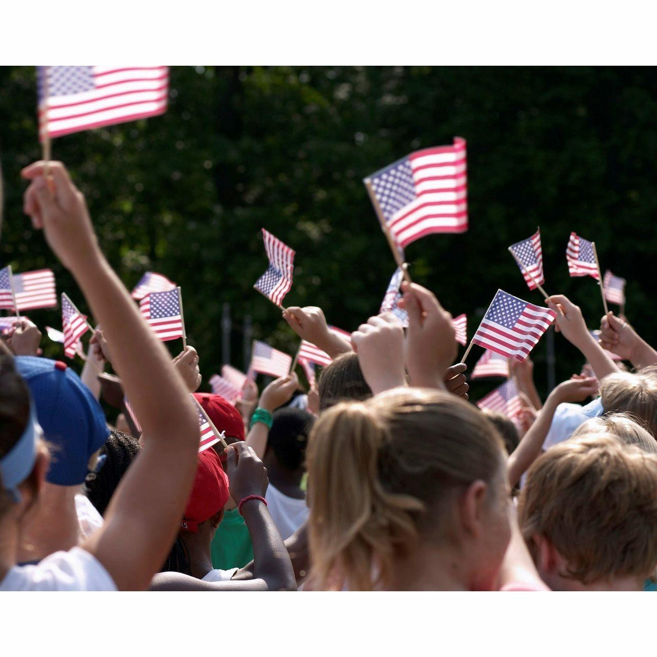 """A crowd of people holding small  4x6"""" American flags on a natural wood stick in their hands and waving them above their heads. The flags are in the shape of a rectangle, with a smaller dark blue rectangle with white stars throughout in the top left corner. To the right of the small rectangle and the rest of the flag are 13 alternating red and white stripes, starting with a red stripe."""