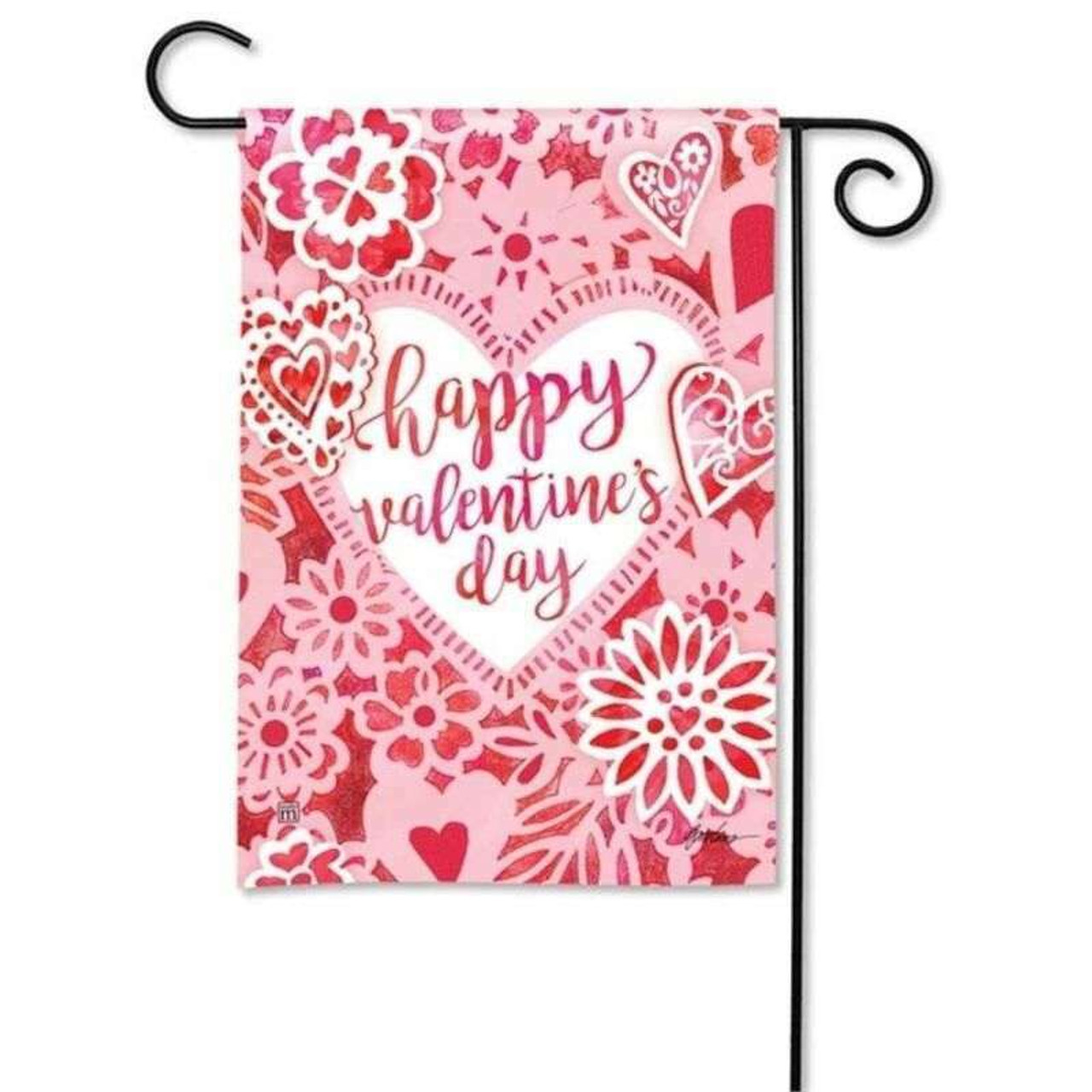 A Valentine's themed garden banner with hues of carnation pink, rose red, and bright white, hangs on a black garden flag pole. In the center of the garden flag is a white heart framed in light pink with cherry red script  spelling 'happy valentine's day.'  The central heart is surrounded and framed with a collage of doily like hearts and flowers.