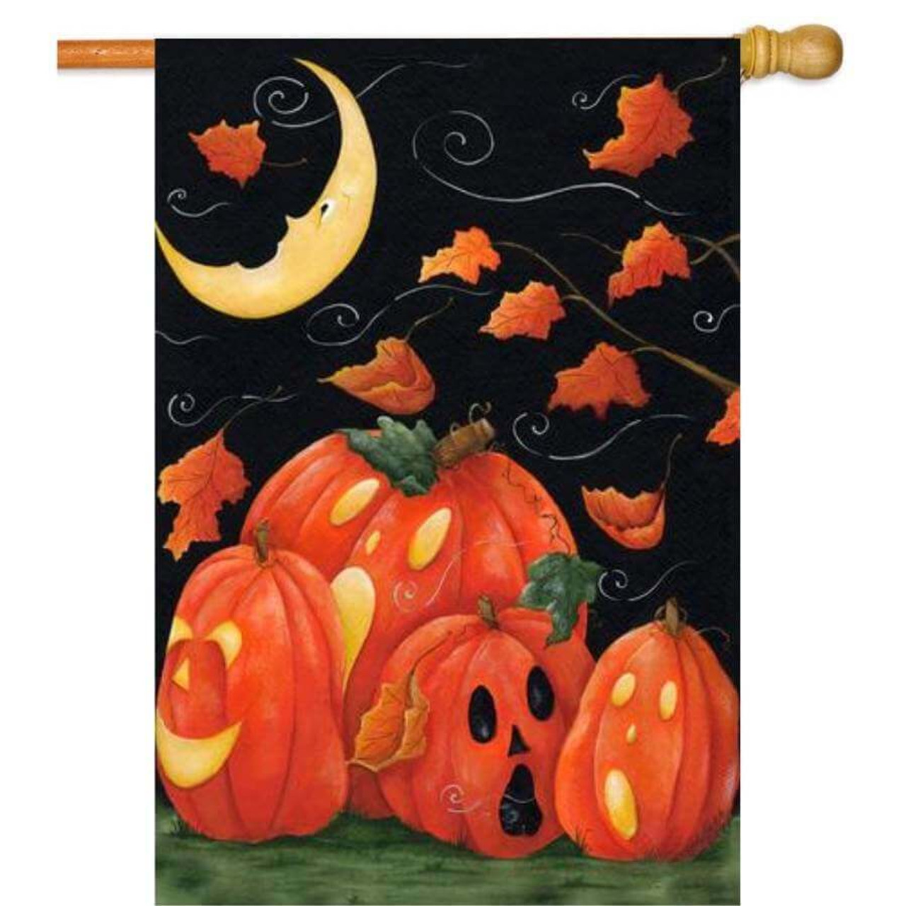 A Halloween flag with a black background. The bottom half has Orange pumpkins with carved faces on grass. The top half has orange leaves flying in the wind and a yellow crescent moon with a face in the top left corner