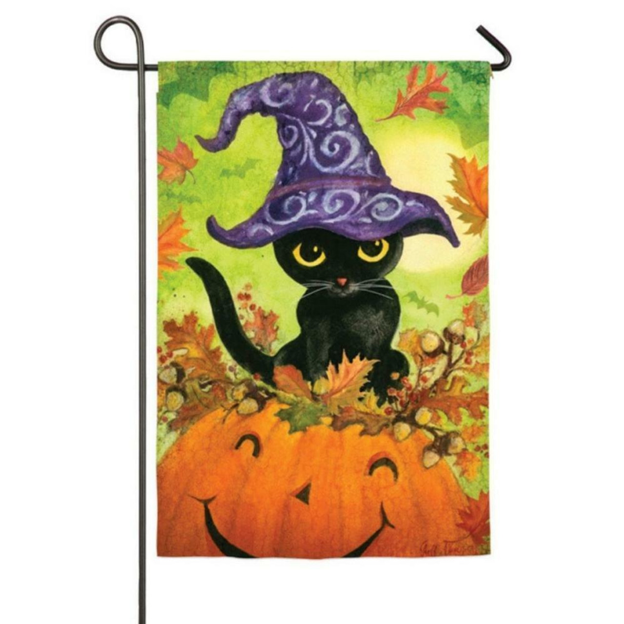 There is a black cat with a black witch's had perched on a bright orange pumpkin with a broad smile.
