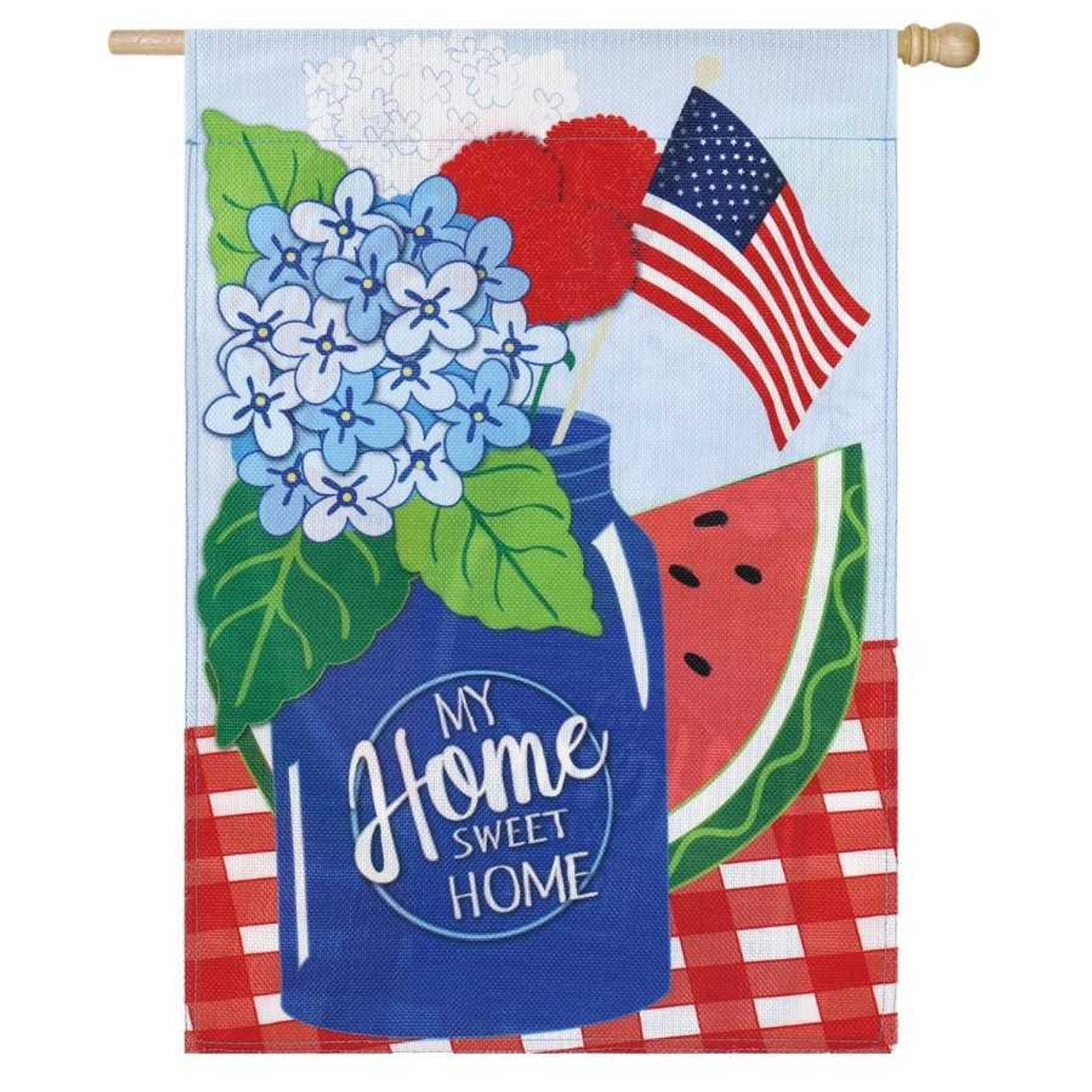 """A flag with a blue mason jar that says """"My Home Sweet Home."""" The jar is on a red plaid table. Inside the jar is blue and red flowers and American stick flag.  Behind the jar is a watermelon. The background is a sky blue."""