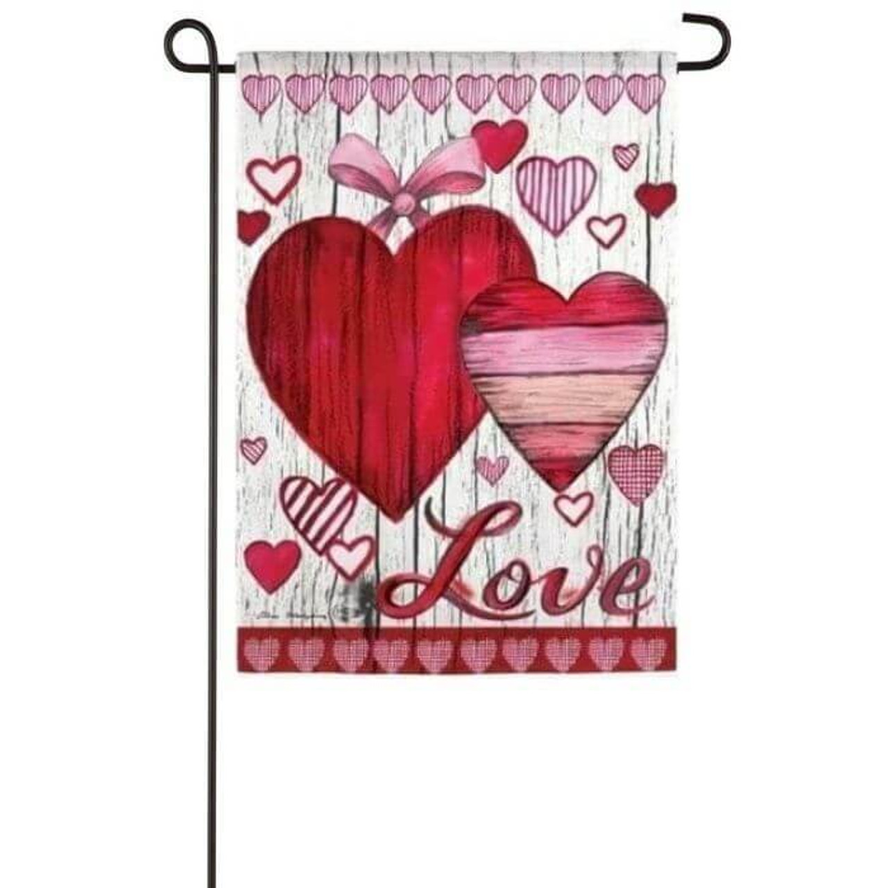 Two red and pink illustrated hearts with a white wooden fence background. There are multiple red hearts all around the  background. The word Love written in red at the bottom in cursive. It is a vertical hanging garden flag. The flag is 12 inches wide and 18 inches long.