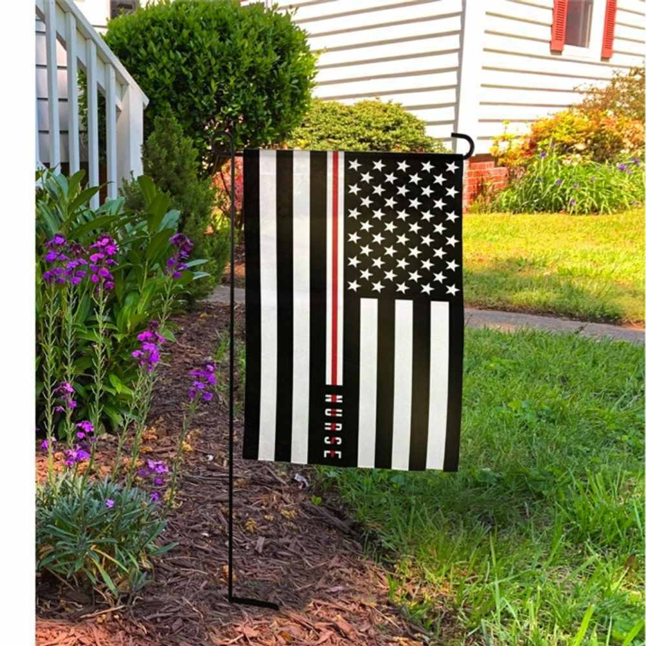 Black and white American flag, the word NURSE is embroidered over a red line on a garden pole in front of a house.