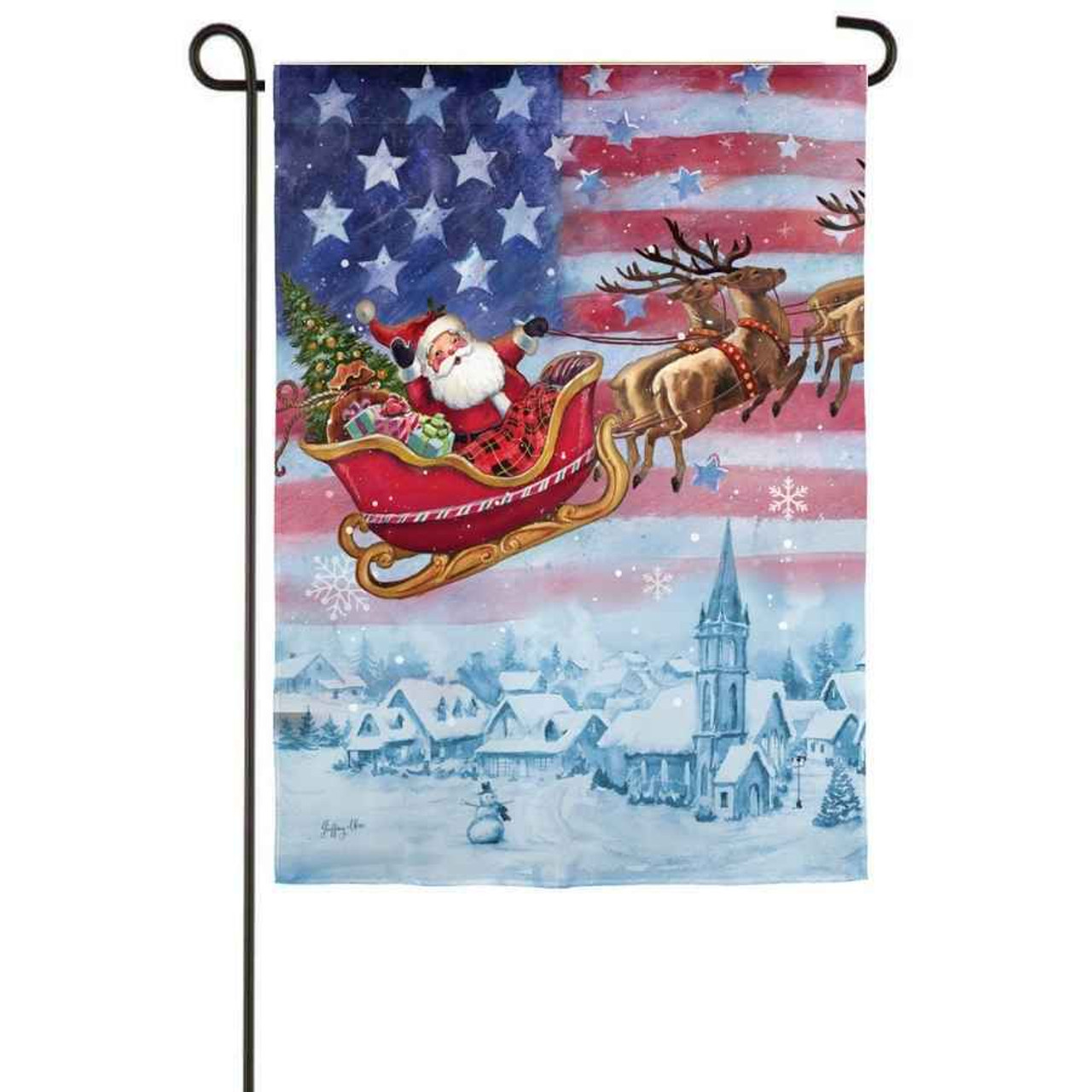 A garden flag with Santa flying in his sleigh over a snowy town. The background has an American flag.