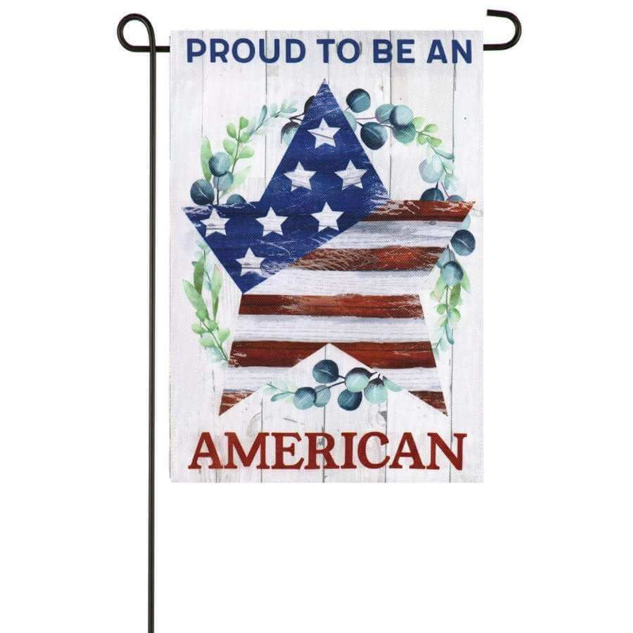 """A patriotic garden flag. The middle has a star filled with the stars and stripes from the American flag. Around the star is a wreath of leaves and blueberries. The background is a white faux wood with """"Proud to be an"""" written on top in blue and """"American"""" written in red on the bottom."""