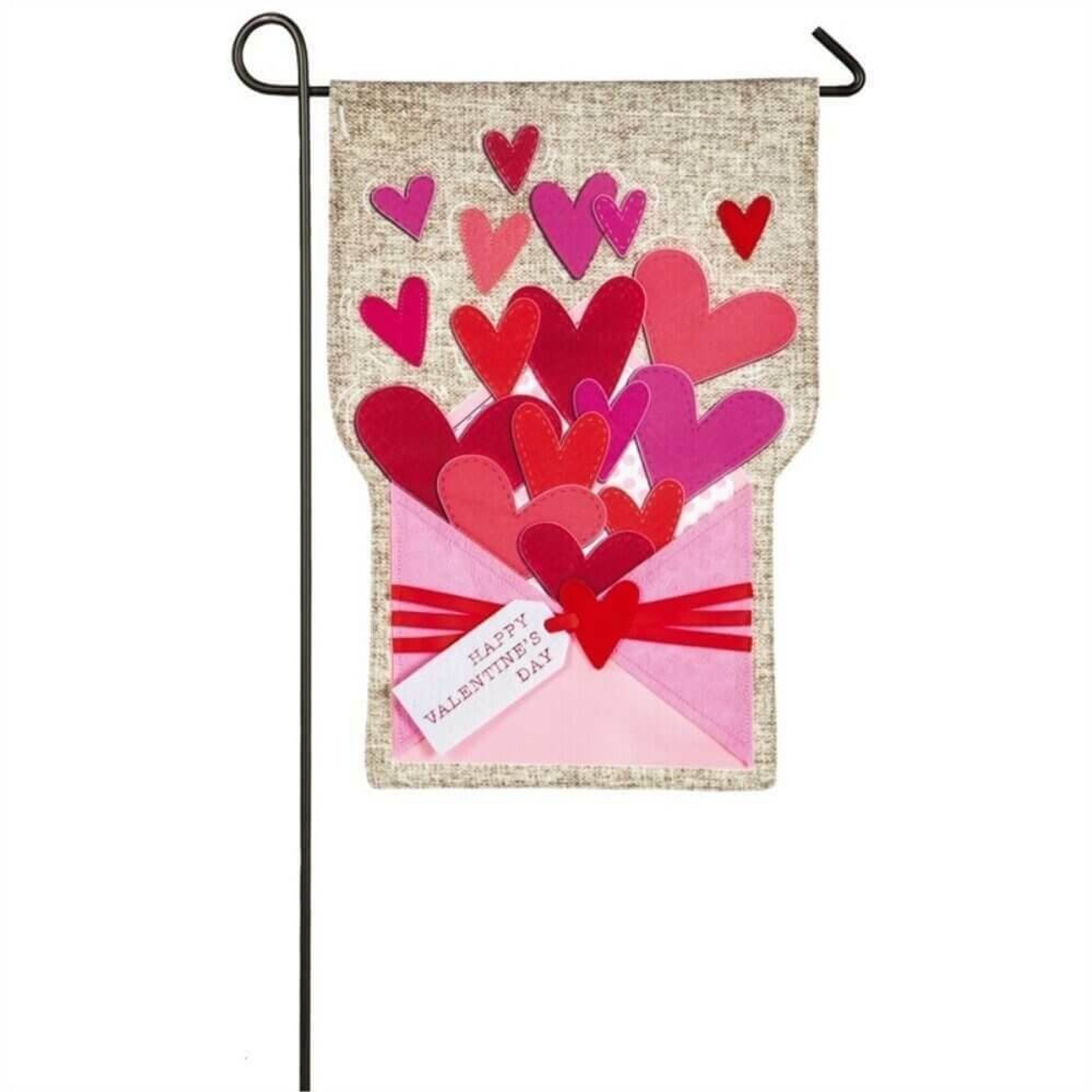 """This garden flag is made of a beige linen material. At the bottom of the flag is a light pink envelope with a gift tag that reads """"HAPPY VALENTINE'S DAY."""" Coming out of the envelope are hearts of different sizes and colors. The color of the hearts are red, light pink, dark pink, and magenta."""