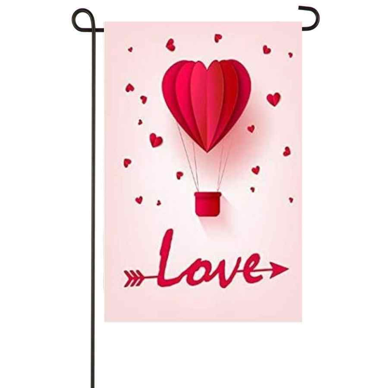 """A light pink garden flag. The middle has a hot pink heart-shaped hot air balloon. """"Love"""" is written on the bottom of the flag with an arrow through it. Small hot pink hearts are scattered around the background."""