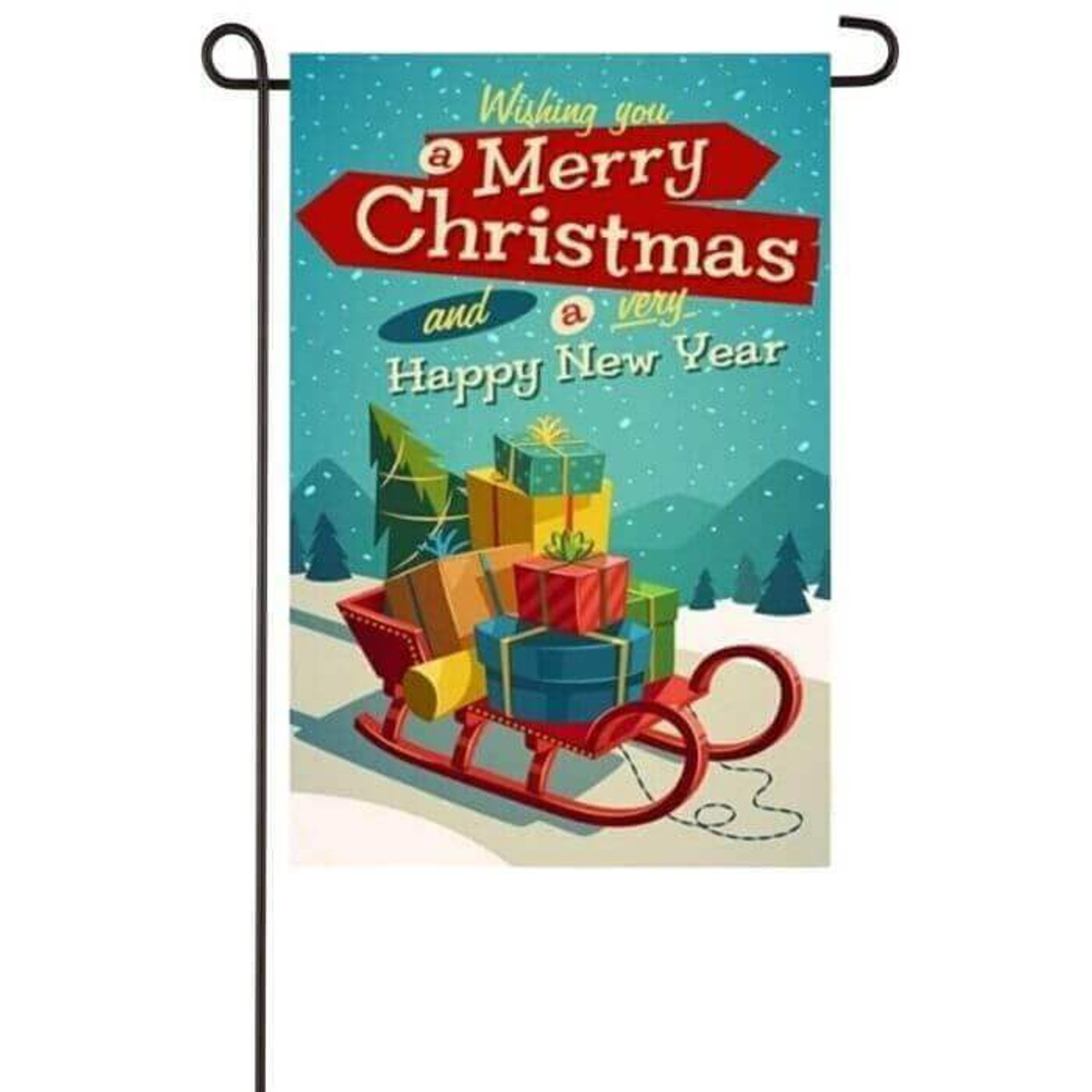 """This garden flag has a retro 70's look to it as it is a red sleigh packed with presents and a Christmas tree going down a snowy mountain with trees in the background. Above the sleigh is the text """"Wishing you a Merry Christmas and a very Happy New Year"""" in different fonts and colors resembling a retro 70's vibe."""