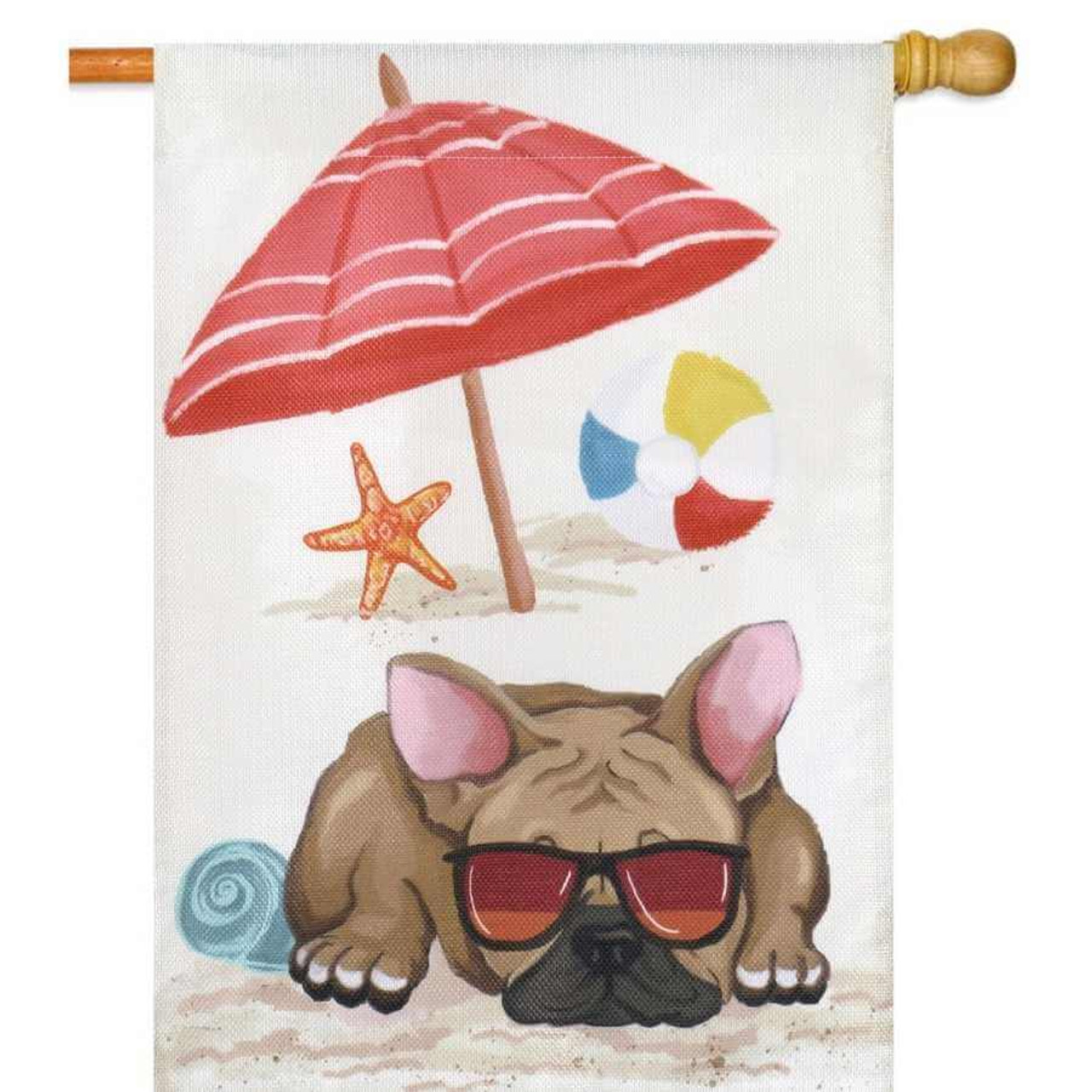 A summer house flag with a brown dog on the bottom portion wearing sunglasses. Behind the dog there is a red umbrella, a starfish, and a beach ball. The background is sand.