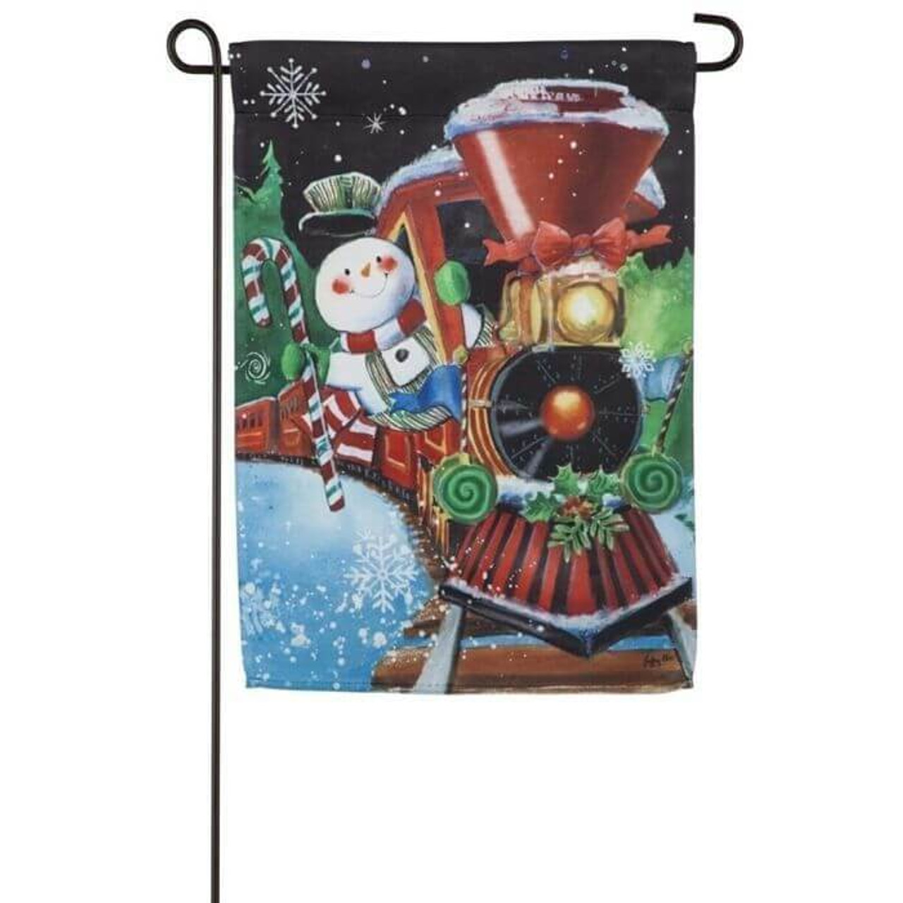 This festive garden flag is a picture of a snowman train conductor riding a red train decorative with red bows, mistletoe, and candy canes. There are trees in the background set on a dark night sky with snowflakes falling.