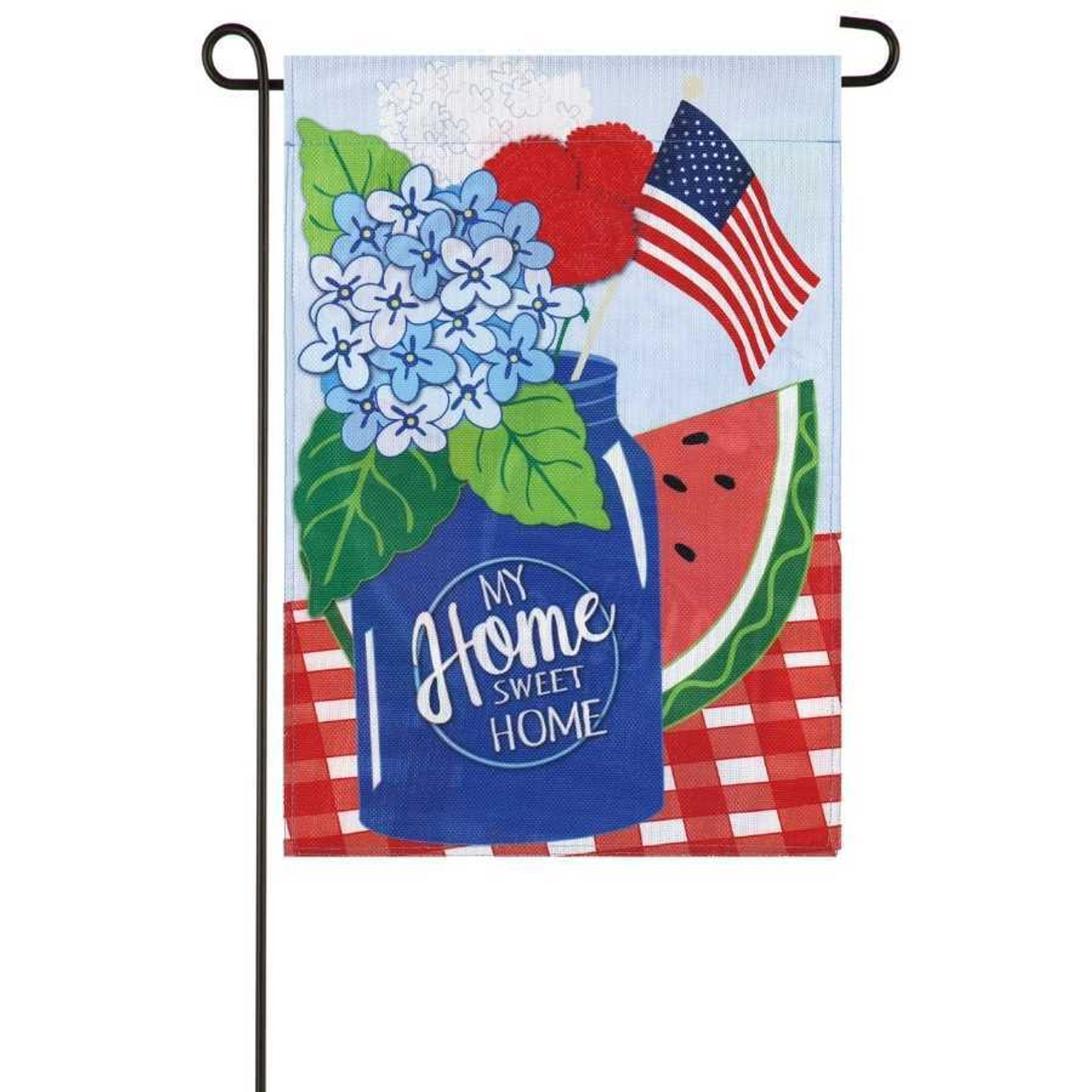 """A garden flag with a blue mason jar that says """"My Home Sweet Home."""" The jar is on a red plaid table. Inside the jar is blue and red flowers and American stick flag.  Behind the jar is a watermelon. The background is a sky blue."""