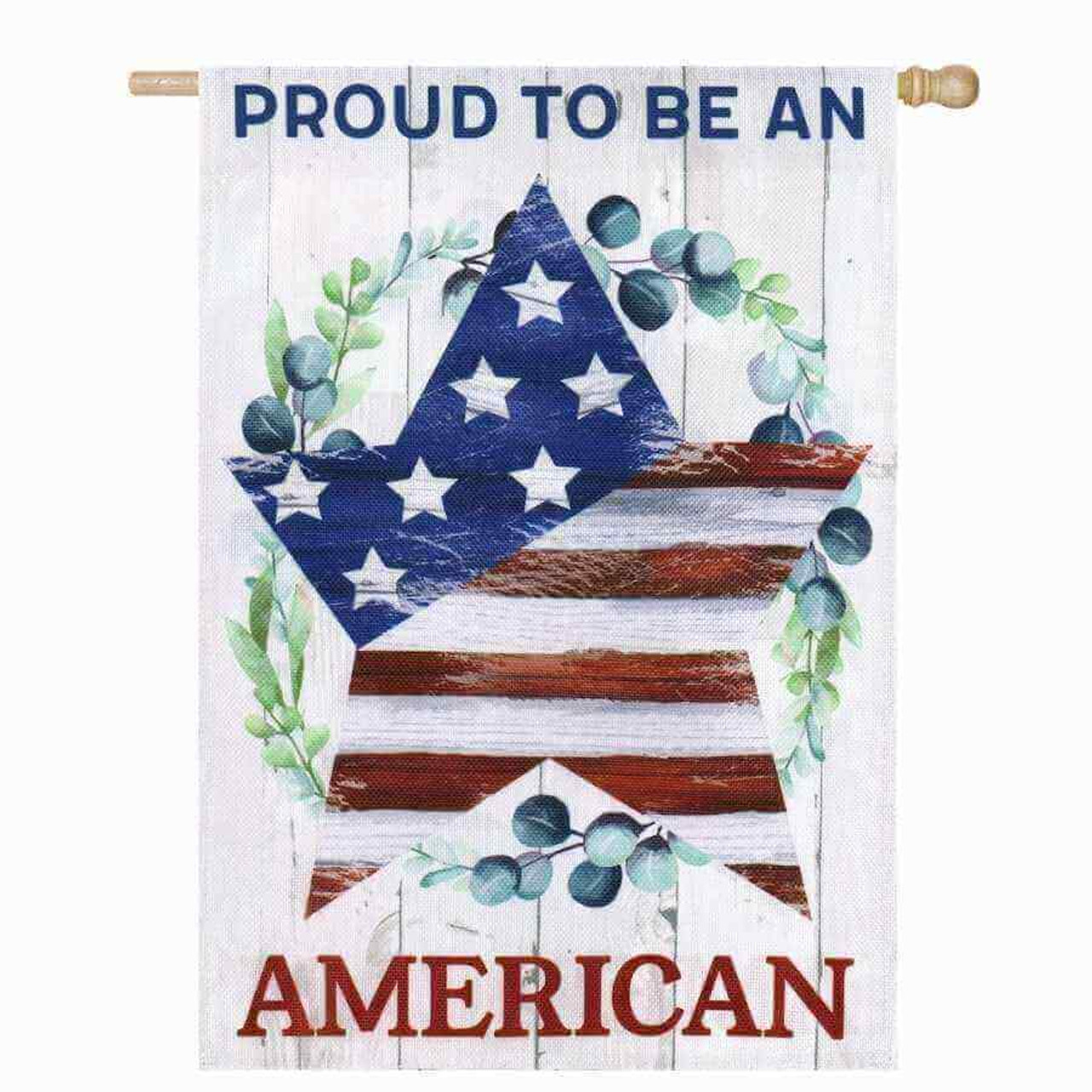 """A garden flag that has a star filled with the stars and stripes from the American flag. Around the star is a wreath of leaves and blueberries. The background is a white faux wood with """"Proud to be an"""" written on top in blue and """"American"""" written in red on the bottom."""