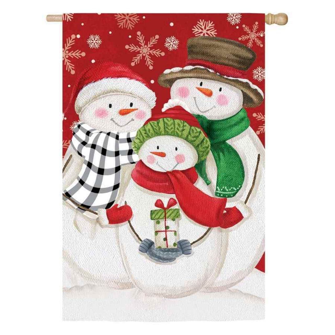 A house flag with a family of 3 snowmen, all wearing hats, gloves, and scarfs. The smallest snowman is holding a present. The background is red with white snowflakes.