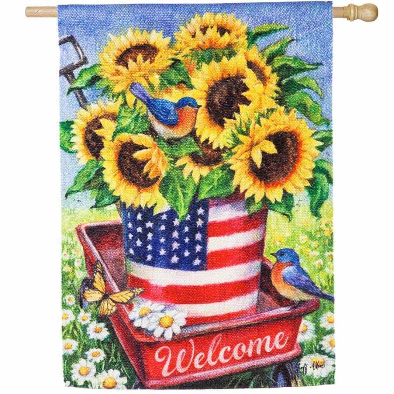 A house flag with a red wagon holding a bucket painted with the American flag. Inside the bucket is sunflowers.