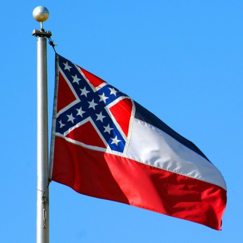 Mississippi state flag flying on a silver aluminum flagpole with a ball on top during a sunny day in Jackson, Mississippi. Photo by Michele B.