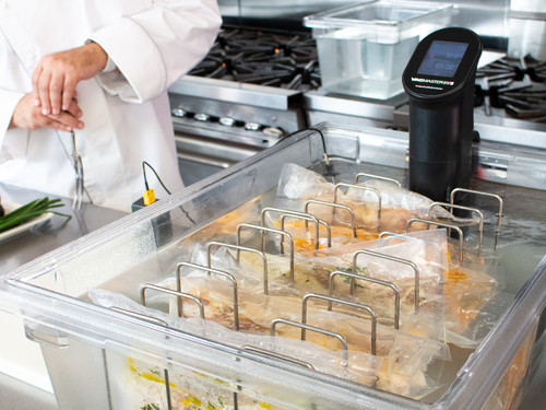 VacMaster SV5 Sous Vide Immersion Circulator with Chef in commercial kitchen cooking full batch of sous vide chicken