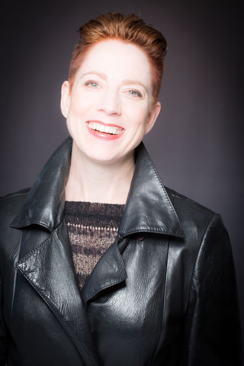 A photo of Kate Story, taken from the torso up. They have pale white skin, green eyes,  and dark red hair that is short at the sides, longer and slicked back on top. Kate is wearing a black leather jacket over a think black sweater.