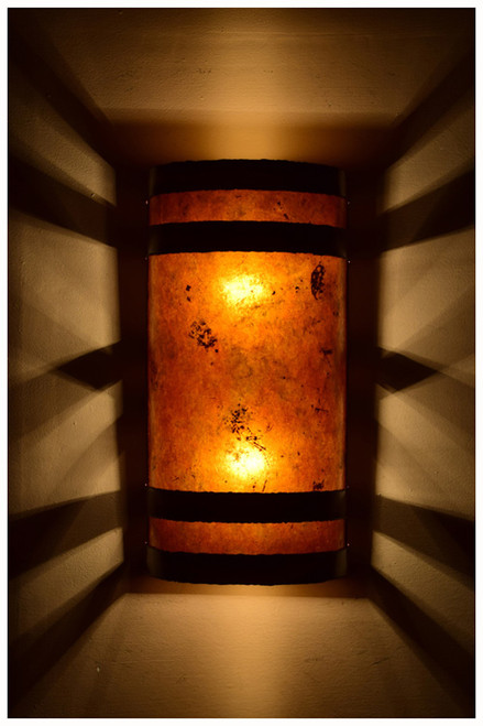 Dark antique copper banded wall light with amber mica at night
