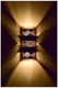 """Burned Ziggurat wall sconce shown at night.  This burned copper provides a more """"artsy"""" feel than the perforated metal version of the the wall light.  Each piece will be slighting different adding to the art of the light fixture."""
