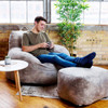 """Big Joe Nestle Vegan Leather Small Bean Bag Ottoman with Adult shown with Optional Chair Cement Room (Adult is 5'11"""" tall)"""