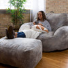 """Big Joe Nestle Vegan Leather Large Bean Bag Ottoman with Adult shown with Optional Loveseat Cement Room (Adult is 5'5"""" tall)"""