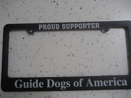 Black license plate holder that says Proud Supporter at the top and Guide Dogs of America on the bottom.