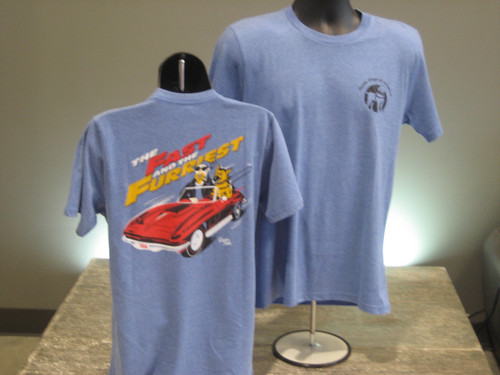 """Fast & Furriest T's. Light heather blue crewneck T-Shirt. Front left chest has Guide Dogs of America logo in black. Back ofshirt has cartoon of red corvette with a german shepherd guide dog, driving his visually impaired partner. Ink colors are white, red, gold and black. Words above image say """"The Fast and the Furriest"""""""