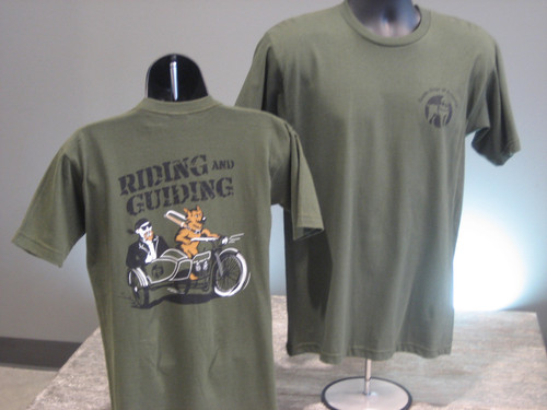 Olive green T-Shirt with a cartoon illustration of a man on a motorcycle with a German Shepherd Gide Dog holding the front handle. The words Riding and Guiding are above the cartoon illustration.