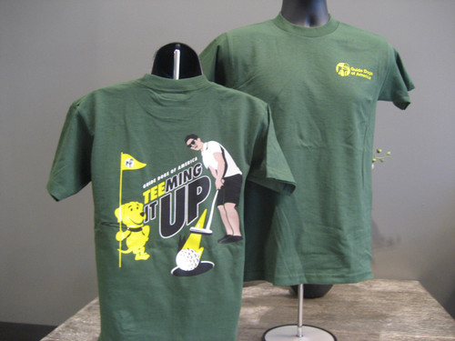 """Forest green crew neck tee. Front left chest pocket has Guide Dogs of America logo in yellow. Back of shirt has cartoon image of man with sunglasses on hitting a golf ball while his guide dog in harness, a yellow lab, holds the flag. Ink colors are black, yellow, and white. Wording above image says """"Guide Dogs of America, Teeming it UP"""""""