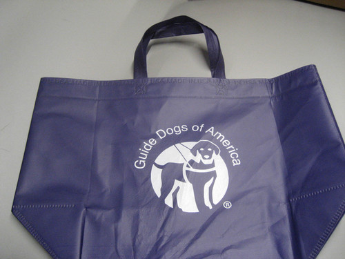 Laminated Navy Blue grocery bag with the white Guide Dogs of America logo in the middle.