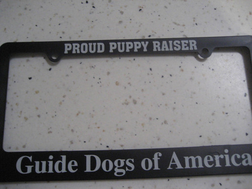 Black license plate holder that says Proud Puppy Raiser at the top and Guide Dogs of America on the bottom.