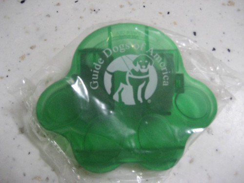 Green chip clip that is shaped like a paw with the Guide Dogs of America logo in the middle.
