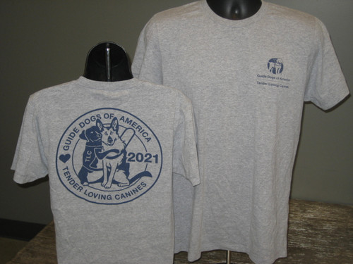 """The front of this Heather Grey T-Shirt has the blue GDA/TLC logo on the left chest. The back features a Labrador dog hugging a German Shepherd Dog in a harness. Text on the shirt says, """"Guide Dogs of America and Tender Loving Canines"""" around the dogs with 2021 beside them."""