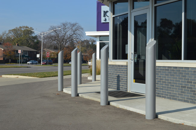 "6"" Light Gray Skyline Decorative Bollard Covers lining a storefront"