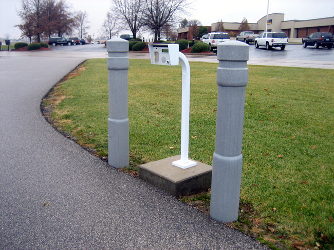 "6"" Architectural Decorative Bollard Covers at a parking lot entrance"