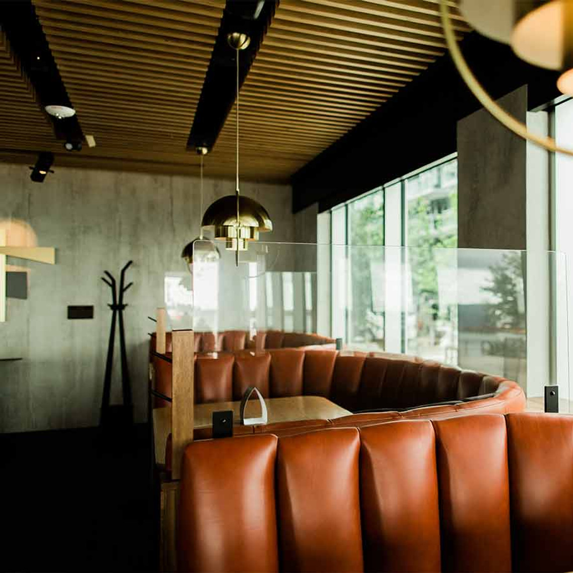 PlexiShield restaurant booth divider separating two standard 1/2 circle booths.