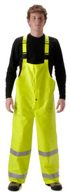 Nasco ANSI Class E FR Rain Bib Overalls - Yong Guy wearing a NASCO Yellow Rain Bib Overalls with 2 reflective silver tape around each leg and a black shirt