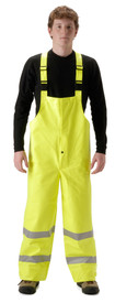 FR CAT 2 High Viz Yellow Rain Bib Overall - Young Man wearing NASCO yellow rain bib overalls with 2 silver reflective tape around both legs below the knee