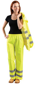 Occunomix Class E Elastic Waist Rain Pants - Front view of  woman wearing Occunomix yellow high visibility rain pants and holding matching rain jacket. Pants have 2 silver reflective tape placed below the knees and elastic waist.