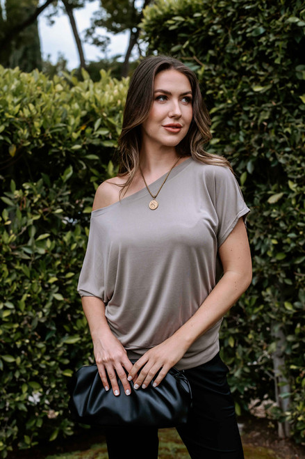 Neutral top features boat neckline that you can wear off shoulder