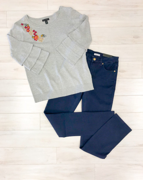 Women's dark rinse straight leg jean shown with gray ruffle sleeve sweater with embroidery