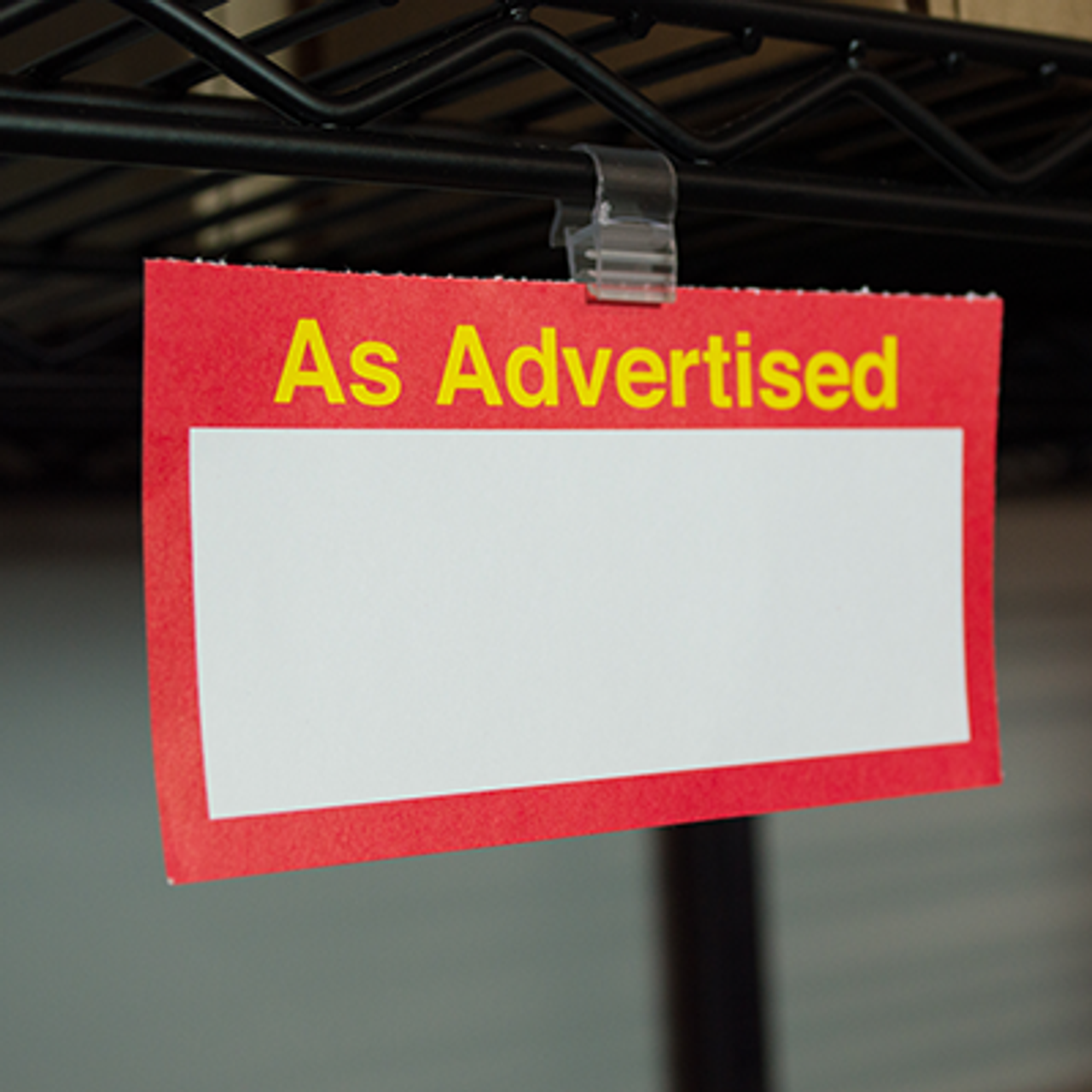 Display signs on wire store fixtures using plastic sign gripper