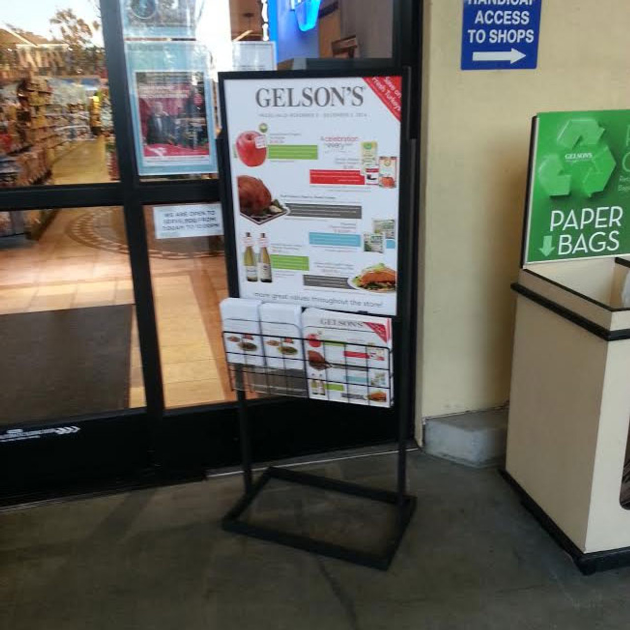 Premium Poster Stand at use by exit to grocery store