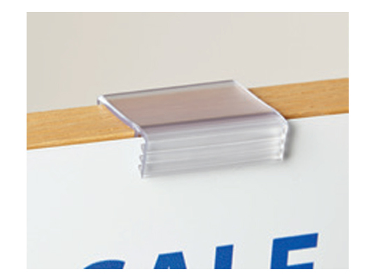 Merchandising sign gripper attaches to wood and glass tables for displaying pricing and product information.